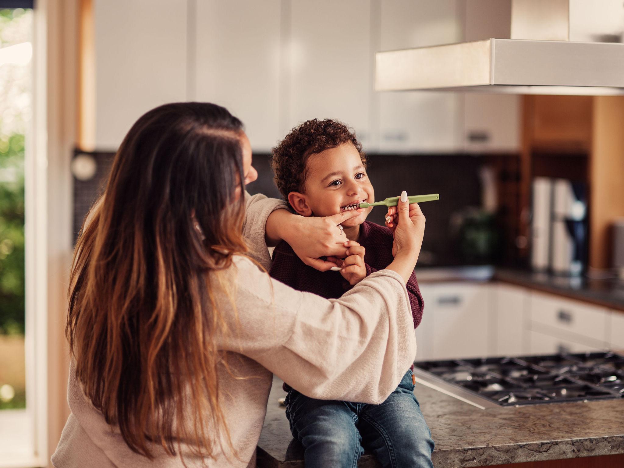 Mamma borstar tänderna på sin son i köket, fotograferat av Satu Knape fotograf i Linköping