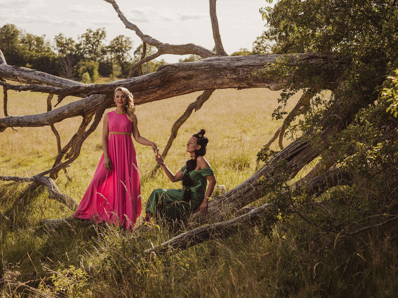 Två kvinnor i vackra klänningar vid ett gammlt träd håller handen, fotograferat av Satu Knape Fotograf i Linköping