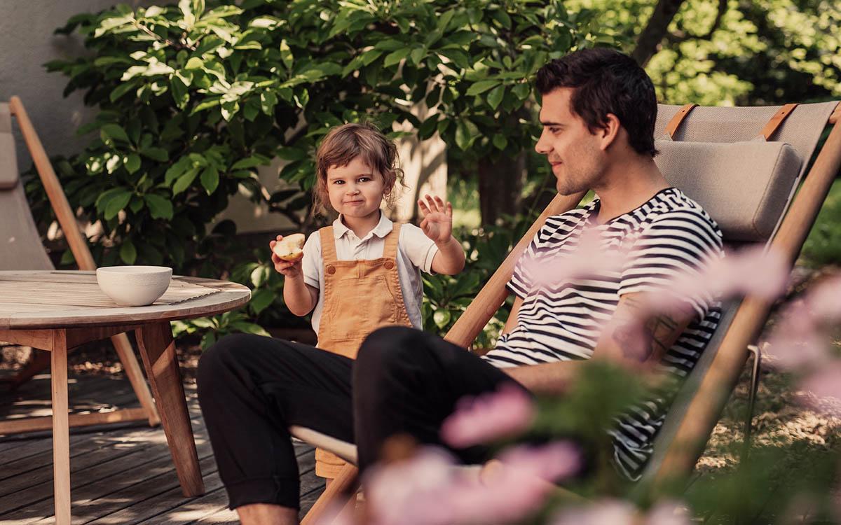 Pappa och liten dotter i trädgården. Flickan äter äpple fotograferat av Satu Knape fotograf i Linköping