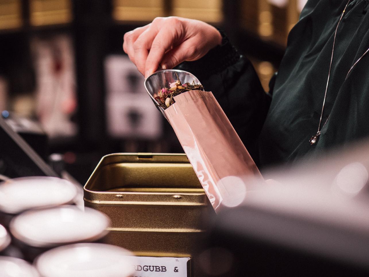 Kassörska häller kaffebönor i påse på Maria på Liljeåkers te & kaffehandel i Linköping fotograferat av Satu Knape fotograf i Linköping
