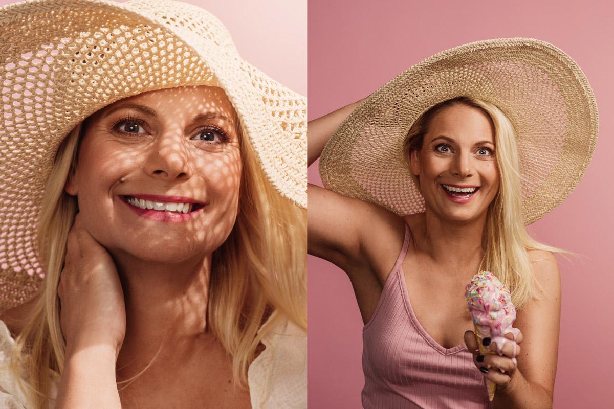 Ung kvinna i solhatt som äter glass fotograferad i studio mot rosa bakgrund av Satu Knape fotograf i Linköping