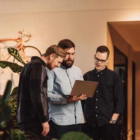 tre unga män med dator på ett företag i Linköping. Fotograferat på plats vid bokad verksamhetsfotografering av Satu Knape Fotograf i Linköping