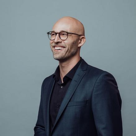 Porträtt av glad man med glasögon fotograferad i studio mot grön bakgrund. Fotograferad av Satu Knape som är fotograf i Linköping