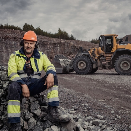 Företagsfotografering utomhus med ung man framför sin gula grävmaskin ute på bygge. Fotograferad i Norrköping av Fotograf Satu Knape fotograf i Linköping