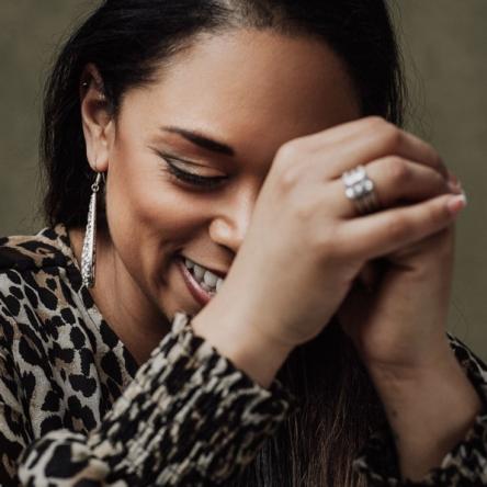 Porträtt av glad kvinna som lutar ansiktet i händerna fotograferad i studio. Fotograferad av Satu Knape som är fotograf i Linköping