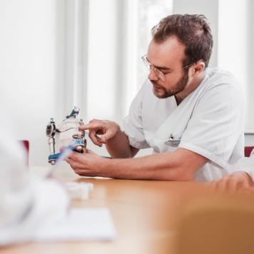 Porträtt av specialisttandläkare som visar en tandprotes i ett mötesrum. Fotograferat av Satu Knape fotograf i Linköping