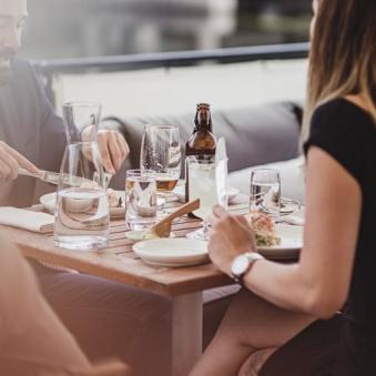 Uppstyrd reklamfotografering med par som äter middag vid dukat bord på restaurang. Motljus och otydliga människor med fokus på dukningen.Fotograferad av Satu knae Fotograf i Linköping