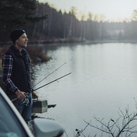 Man i väst och skjorta ute på fisketur en tidig morgon innan solen helt har gått upp. Kall morgon. Fotograferat av Satu Knape Fotograf i Linköping
