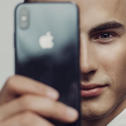 Kreativt portätt av ung man med telefon framför ögat. Fotograferat i studio med blixt mot ljus bakgrund av Satu Knape Fotograf i Linköping